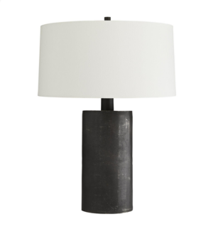 Profis Lamp Dark and mysterious, this table lamp brings light even with its own inky hue. It's completely crafted from blackened aluminum, one of our first pieces to adorn this rich finish. The result is a sort of matte graphite look, with a bit of a raw effect, which brings out the industrial edge of this lamp. It is topped with an off-white linen drum shade with white cotton lining. H: 29.5IN Dia: 22.00IN